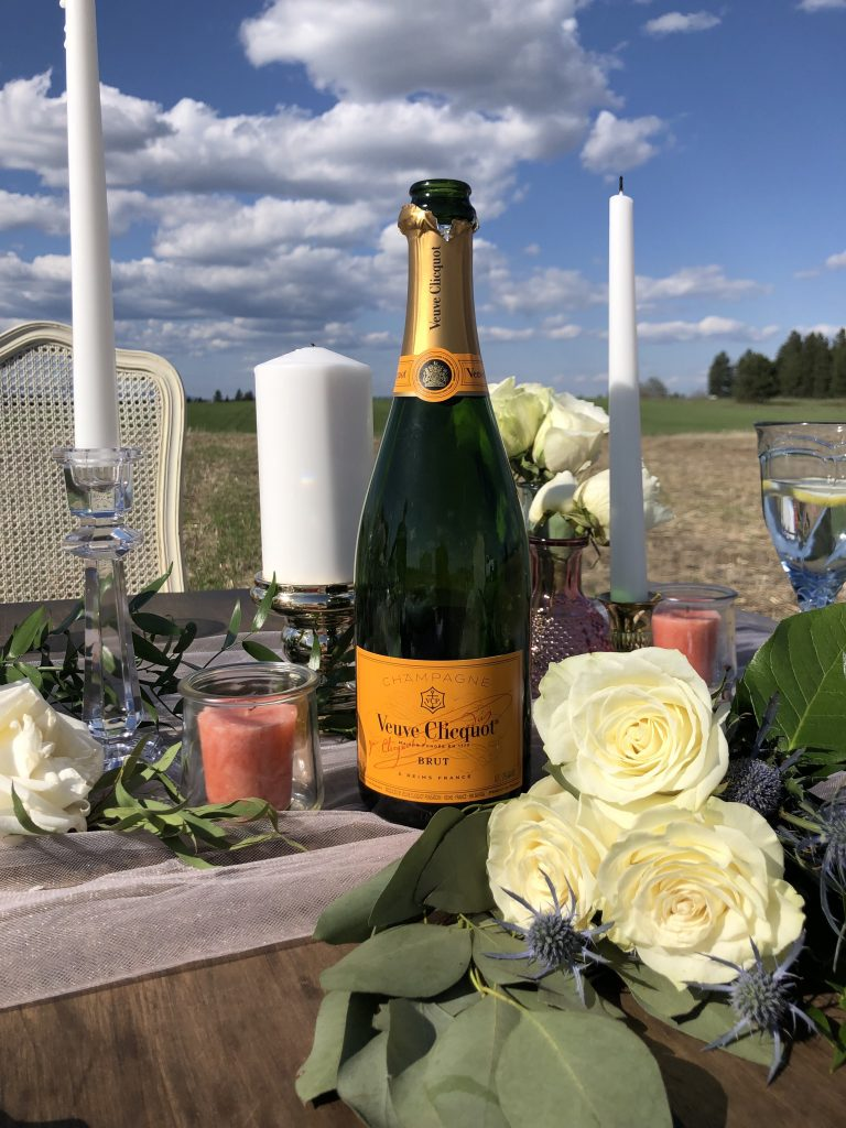 champagne and roses on a wedding table in a field