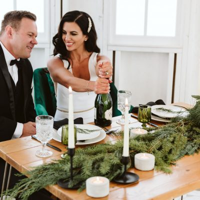 bride and groom in white modern barn drinking champagne
