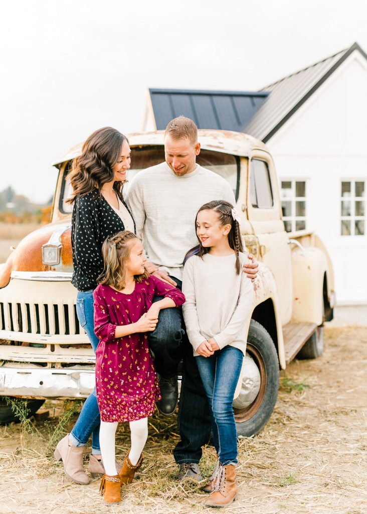fall family photo in front of old truck and white barn flower shop