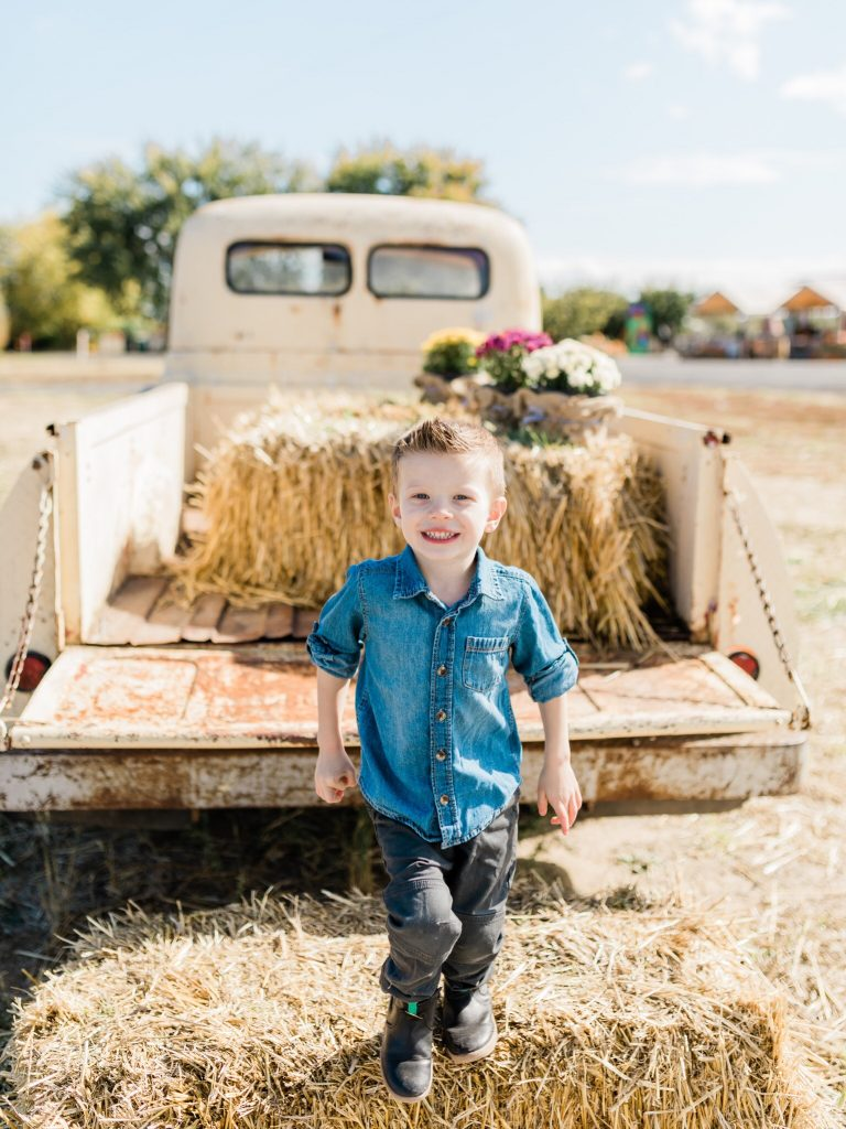 boy jumping from hay bale off old pickup truck