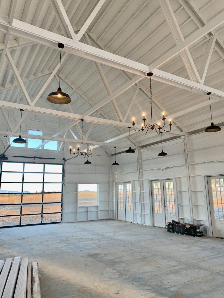 white modern barn with black glass garage door