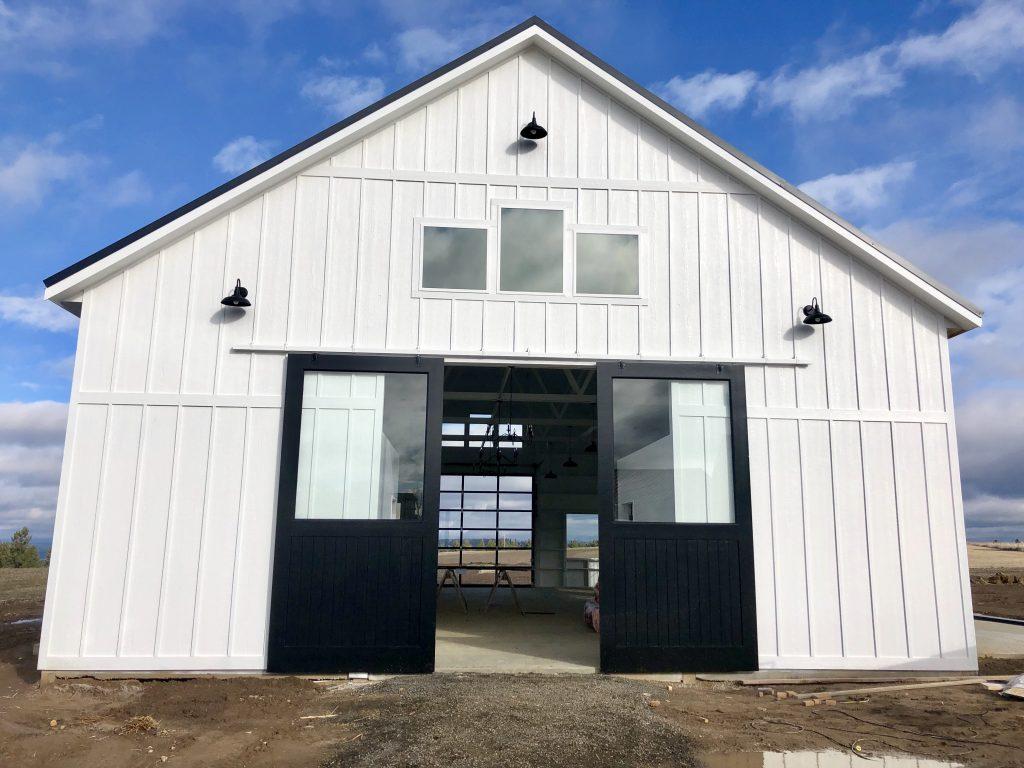 white barn with black barn doors gooseneck lights